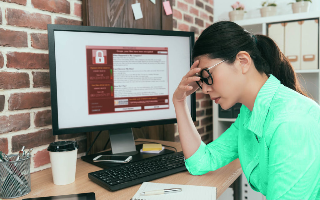 A photo of a woman holding her head in her hand when she realizes that her computer is infected with ransomware