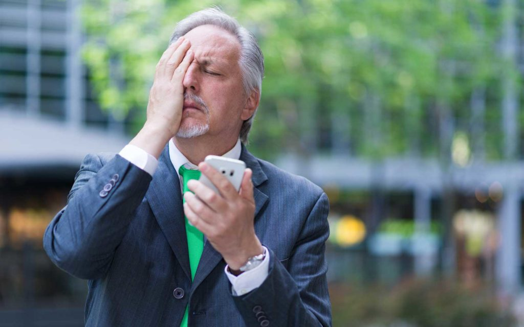 What is vishing example: A stock image of a worried businessman with a hand over his face